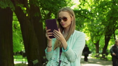 Pretty girl wearing sunglasses and browsing internet on tablet in the park Stock Footage