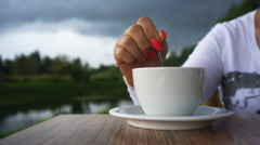 Woman's hand with red nail polish and a cup of coffee on the background of Stock Footage