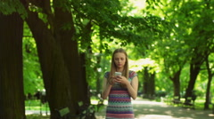 Absorbed girl walking in the park and texting on smartphone Stock Footage