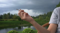Female hand with a cigarette on a background of a beautiful summer landscape Stock Footage
