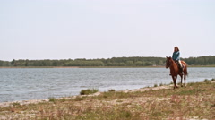 Female Riding Brown Horse near Water Stock Footage
