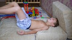 The child having fun on the pillows and laughs Stock Footage