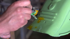 Man with tattoos color the details of the motorcycle in the garage Stock Footage