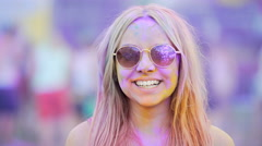 Girl in sunglasses covered in colorful dyes smiling, blowing air kiss to camera Stock Footage
