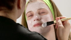 Close up hand of cosmetologist applying cream mask on face of teenage girl Stock Footage
