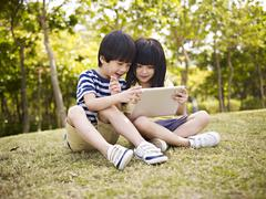 Two asian children using tablet outdoors Stock Photos