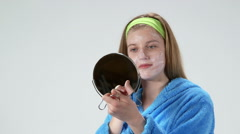 Teenage girl with problem skin wiping off homemade facial mask Stock Footage
