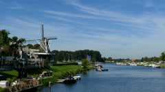 Dutch windmill on the banks of the river Stock Footage