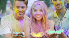 Happy young people holding coloured powder in hands, blowing dyes to camera Stock Footage
