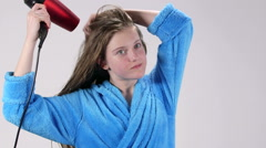 Teenage girl blow drying her wet long hair with hairdryer after shower Stock Footage