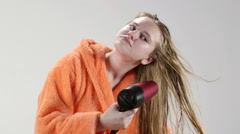 Teenage girl in bathrobe blow drying her wet long hair with hairdryer Stock Footage