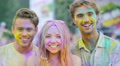Joyful young people smiling to camera, clapping hands covered in color powder 4k or 4k+ Resolution