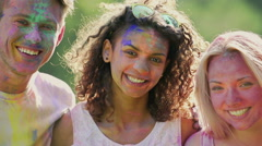 Excited young people with faces covered in colours, friends smiling for camera Stock Footage