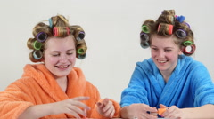 Funny teen girls in hair curlers with nail polish collection painting nails Stock Footage