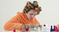 Teenage girl in hair curlers with nail polish collection painting nails at home Stock Footage