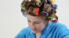 Teenage girl in hair curlers doing manicure at home painting nails Stock Footage