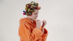 Teenage girl wearing bathrobe in hair curlers applying nail polish on fingernail Stock Footage