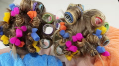 Heads of two young girls in colorful hair curlers doing manicure at home Stock Footage