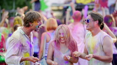 Cheerful young people throwing colorful powder in air, dancing at festival Stock Footage