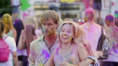Happy friends dancing to music in good mood, enjoying color festival atmosphere Stock Footage