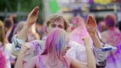 Drunk man covered in Holi colors performing crazy dance, young woman laughing Stock Footage