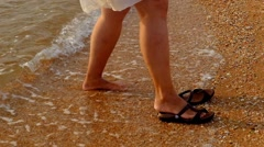 Woman put on slippers and walking on beach sunset steadicam shot Stock Footage