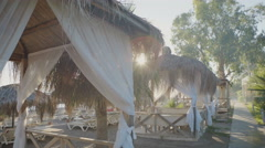Empty tropical beach with palm trees, and summer bungalo at sunset Stock Footage