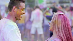 Energetic young couple covered in coloured powder dancing to music and smiling Stock Footage
