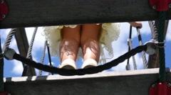 Children playground outdoors kids girl and boy legs walk over suspension bridge Stock Footage