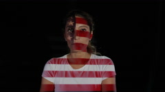 4K USA flag projected onto the face & body of female model on black background Stock Footage