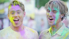 Two cheerful male friends having fun at outdoor color festival, giving high five Stock Footage