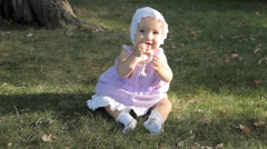 A baby girl in a bonnet sitting on the grass lit by setting sun Stock Footage