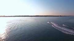 Aerial of person water skiing at sunrise on sea 4K Stock Footage