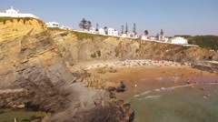 People relax on the beach Zambujeira de Mar near the rocks aerial view Stock Footage