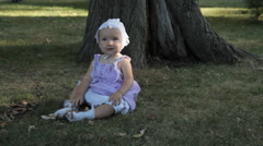 A baby girl in a bonnet sitting on the grass and holding a stick Stock Footage
