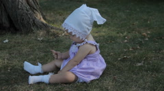 A baby girl in a bonnet sitting on the grass and tears it Stock Footage