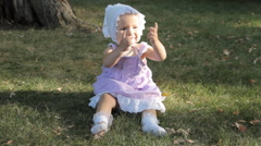 A baby girl in a bonnet sitting on the grass and clapping her hands Stock Footage