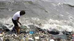 Woman scavenging plastic materials from sea Stock Footage