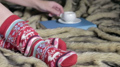 Female legs in Christmas socks with a book Stock Footage