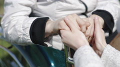 Caring young support girl holding the hand of elderly woman in a wheelchair Stock Footage