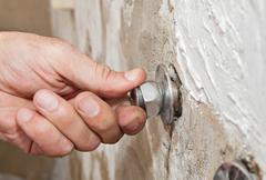 Repair wall mount faucet, close-up hand plumber turns eccentric tap. Stock Photos