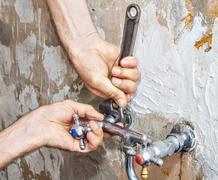 Dismantling of old faulty faucet, hands of plumber with wrench. Stock Photos