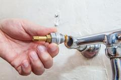 Close-up hands plumber install tap valve to kitchen water faucet. Stock Photos