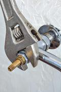 Close-up plumbers adjustable wrench tightens valve faucet. Stock Photos