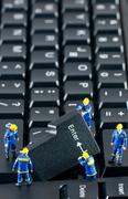Team of construction workers working on a computer keyboard Stock Photos