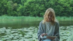 Beautiful girl using Tablet PC sitting near lake in city park. Stock Footage