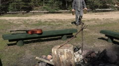 Hiker carries wooden logs to the fire site Stock Footage