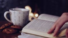 Female hands putting a book near a cup of tea by the fireplace Stock Footage