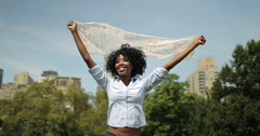 Young adult black woman in city park walking waving scarf Stock Footage
