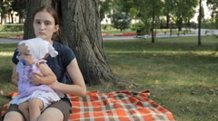 A young nanny putting a baby girl down on a blanket. The baby girl creeps away Stock Footage